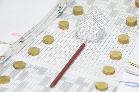 pencil point: Brown pencil point to house on finance account between step pile of gold coins and overload of paperwork as background. Stock Photo