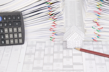 dual: House and pencil on finance account have calculator place vertical and dual pile overload document of report with colorful paperclip as background. Stock Photo