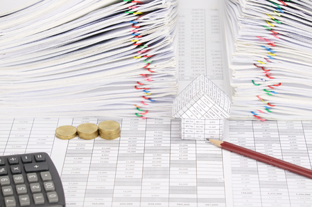 money stack: Pencil and house with step pile of gold coins on finance account have calculator and dual pile overload document of report with colorful paperclip as background.