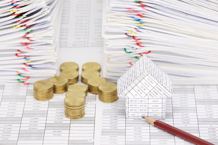 dual: Close up house and pencil with step pile of gold coins on finance account have dual pile overload document of report with colorful paperclip as background.