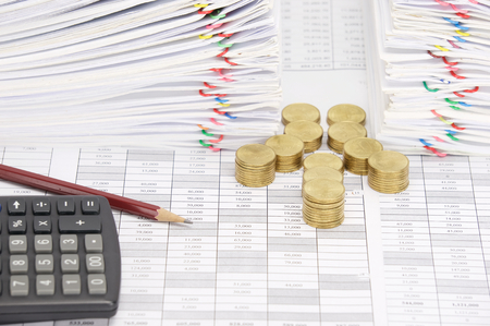 workload: Step pile of gold coins and pencil with calculator on finance account have dual pile overload document of report with colorful paperclip as background. Stock Photo