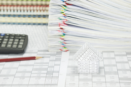 workload: House on finance account have blur pencil with calculator and pile paperwork of report with colorful paperclip with stack notebook as background. Stock Photo