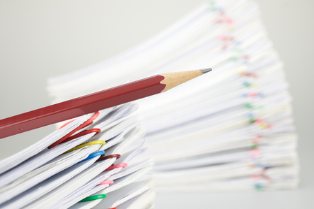 workload: Close up pencil on document have blur pile overload paperwork of report and receipt with colorful paperclip place on white background. Stock Photo