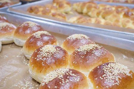 oven tray: Close up brown bread baked with white sesame on aluminium oven tray.