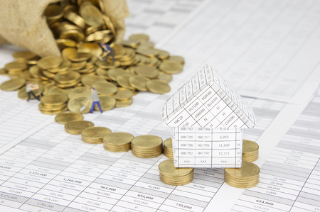 Close up house on pile of gold coins on finance account have blur gold coins overflow from brown sack with construction worker as background. Stock Photo