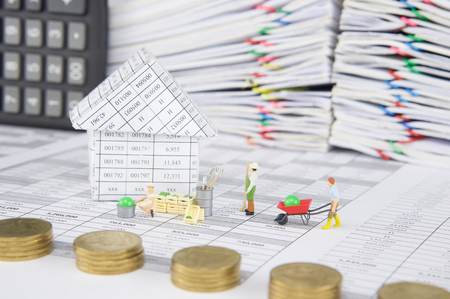 House with farmer on finance account have blur pile of gold coins with calculator place vertical and pile overload paperwork of report and receipt with colorful paperclip as foreground and background.
