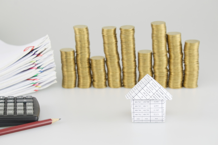 House have blur pile of gold coins with pile paperwork of report and receipt with colorful paperclip and calculator with pencil on white background.