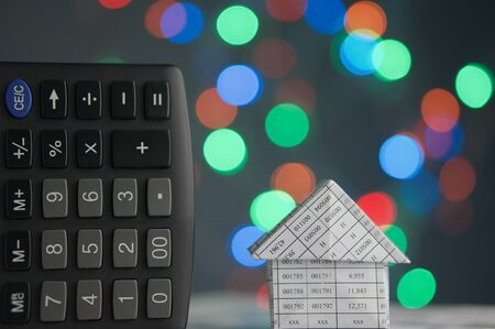 House and calculator have colorful bokeh circle or defocused of glitter at night as background.