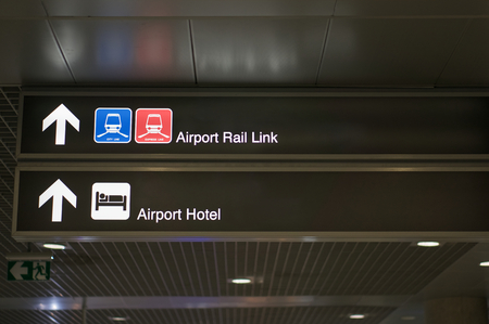 Airport rail link and airport hotel information board sign with white character on black background at international airport terminal.