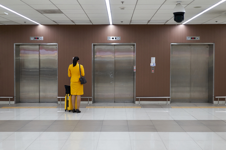 Air hostess with yellow uniform is checking her flight schedule and waiting elevator at the international airport terminal with copy space. Stockfoto