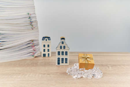Golden gift box on ice have blur house and stack of overload paperwork report on wooden table with white background and copy space. Business and finance on happy new year and merry christmas concept. Stok Fotoğraf