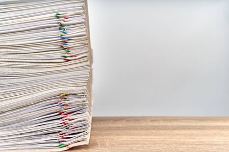 Pile of overload paperwork report of sale with colorful paper clip on wooden table with white background and copy space. Stack document is high as work hard. Business and finance concept success.
