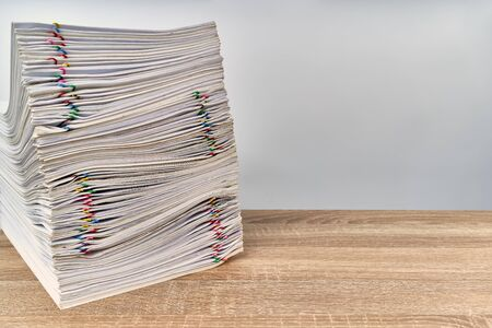 Stack of overload paperwork report of sale with colorful paper clip on wooden table with white background and copy space. Stack document is high as work hard. Business and finance concept success.