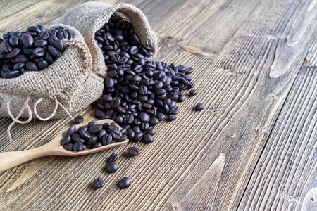 Close up stack of coffee bean on wooden spoon and in brown sack place on wooden background with copy space. Coffee bean full of sack as abundant. Food and drink concepts.
