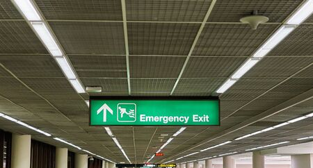 Emergency exit information board sign with white character on green background at international airport terminal.