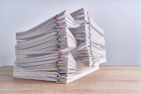 Pile overload paperwork of report of sale and receipt with colorful paperclip place on wood table and white background with copy space. Business and finance concepts successful photography. Imagens