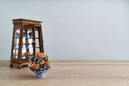 Stack of Thai caramel or Kalamare with sesame on pedestal tray have blur cabinet with Thai dessert place on wood table with white background and copy space. Sweet and gummy snack of Thai food. Imagens