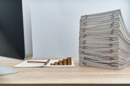 Step pile of gold coins and pencil on notebook with stack of overload paperwork report of sale on wooden table have blur computer on foreground with white background and copy space. Business and finance concept success.