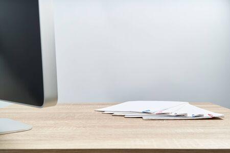 Il rapporto di lavoro di ufficio occupato della vendita e della ricevuta con la graffetta sulla tavola di legno ha il computer di sfocatura in primo piano con lo sfondo bianco e lo spazio della copia. Successo del concetto di affari e finanza. Archivio Fotografico