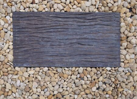 Piece of dark rectangle wood on pebble in garden as background with copy space. Stok Fotoğraf