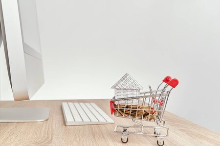 House on gold coins in shopping cart on wooden computer table with white background and copy space. Business and finance concepts shopping online photography.