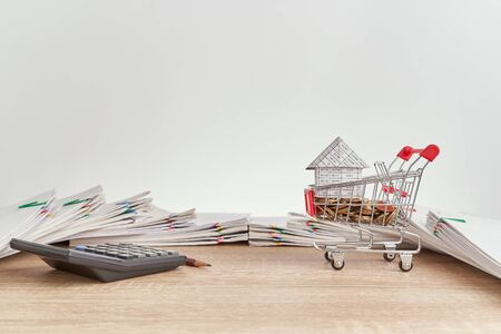 House on gold coins in shopping cart and calculator with pencil on wooden table have pile of paperwork of report of sale and receipt with colorful paperclip as background and copy space.