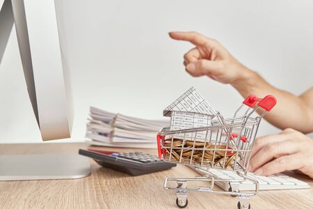 House on gold coins in shopping cart have blur man pointing finger for checking sales of shopping online concept and pile report of sale on wooden computer table with white background and copy space.