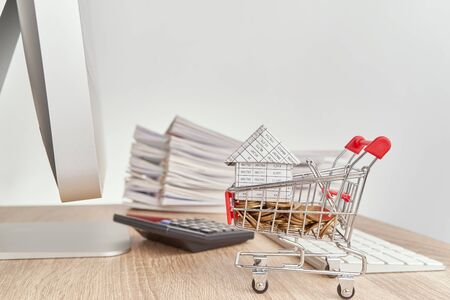 House on gold coins in shopping cart have blur calculator with pencil and pile report of sale on wooden computer table with white background and copy space. Business concepts shopping online. Stok Fotoğraf