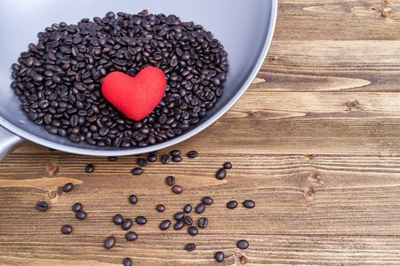 Close up red heart on pile of coffee bean in iron pan with spread coffee bean on old wooden table and copy space.
