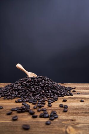 Wood spoon put on pile of coffee bean overflow on old wooden table with black background and copy space. Stok Fotoğraf