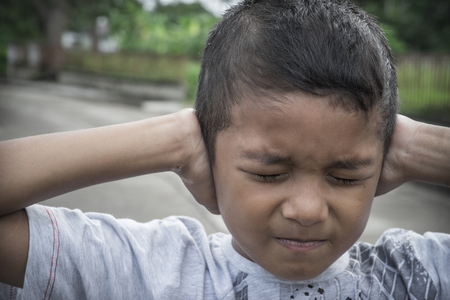 dissappointed: Young Asian boy covering his ears with his hands Stock Photo