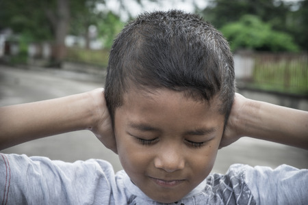 lonliness: Young Asian boy covering his ears with his hands Stock Photo