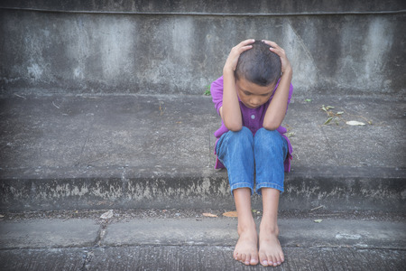 poor: Young Asian homeless child looking scared, alone and in need of help Stock Photo
