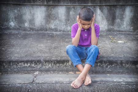 Young Asian homeless child looking scared, alone and in need of help Archivio Fotografico