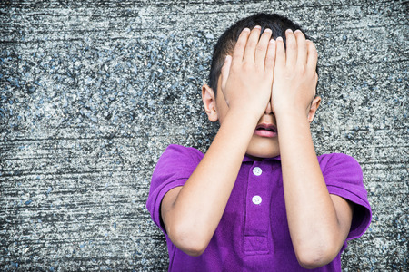 fear face: Young Asian boy using his hands to protect himself from physical abuse Stock Photo