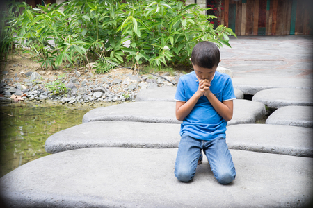 dissappointed: Young Asian boy kneeling on rocks to pray