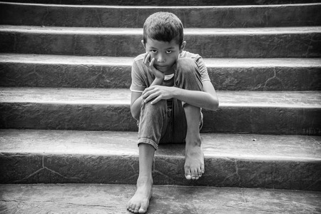 Young Asian homeless child looking scared, alone and in need of help Foto de archivo