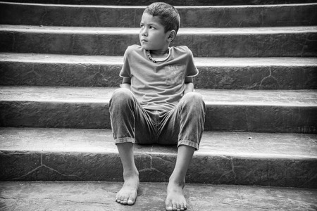 lonliness: Young Asian homeless child looking scared, alone and in need of help Stock Photo