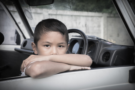 dissappointed: Young Asian boy looking out of a car window