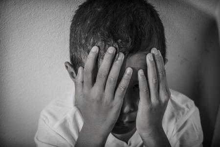 asustadotdo: Muchacho asiático joven que usa las manos para protegerse de los abusos físicos