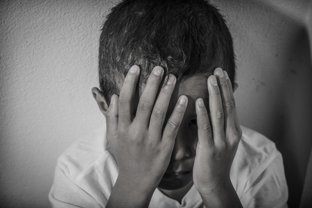 alone in the dark: Young Asian boy using his hands to protect himself from physical abuse Stock Photo