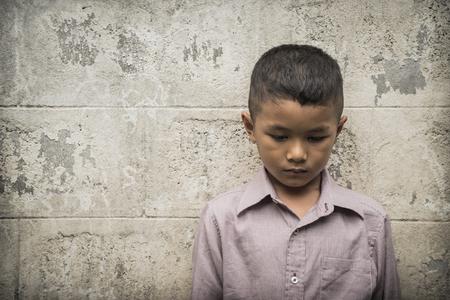 Jonge Aziatische dakloze kind op zoek bang, alleen en in behoefte aan hulp