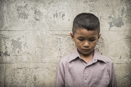alone: Young Asian homeless child looking scared, alone and in need of help Stock Photo