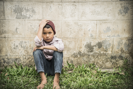 Young Asian homeless child looking scared, alone and in need of help Stock Photo