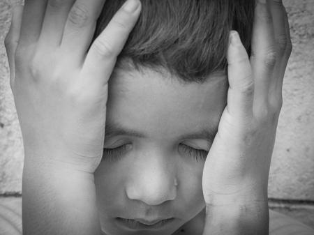 niños pobres: Muchacho asiático joven que usa las manos para protegerse de los abusos físicos