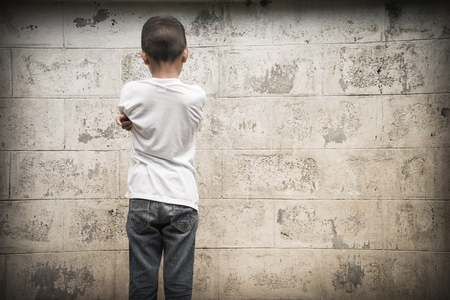 dissappointed: Young Asian boy looking at a wall Stock Photo