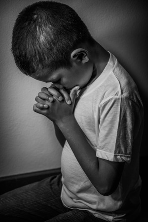 young fear: Young Asian boy kneeling to pray