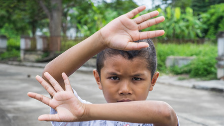 dissappointed: Young Asian boy using his hands to protect himself from physical abuse Stock Photo