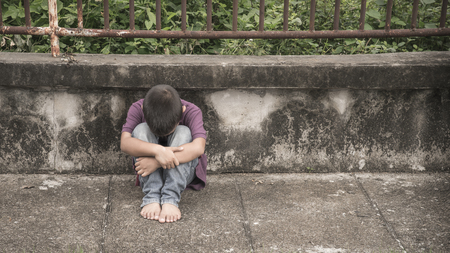 A young homeless Asian boy sitting on the side of the road covering his face. He is at high risk of abuse and trafficking