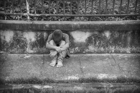 poor health: A young homeless Asian boy sitting on the side of the road covering his face. He is at high risk of abuse and trafficking